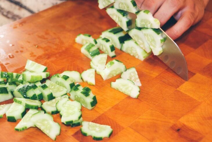 person slicing cucumber vegetable