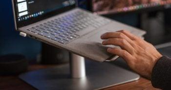 crop faceless man using laptop on stand