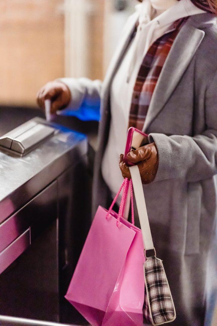 woman passing through checking electronic turnstile in subway
